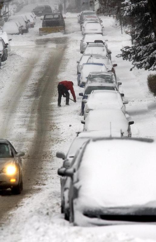 9. Мужчина расчищает снег перед своим автомобилем в Монреале.