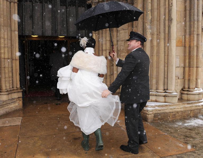 10) Грейс Сентаму, дочь архиепископа Йоркского доктора Джона Сентаму, в резиновых сапогах и свадебном платье, заходит в Йоркский кафедральный собор, чтобы обвенчаться с Тимоти Беверстоком. Невеста была вынуждена так обуться из-за сильной снежной бури в Йорке. (AP Photo/John Giles-PA)