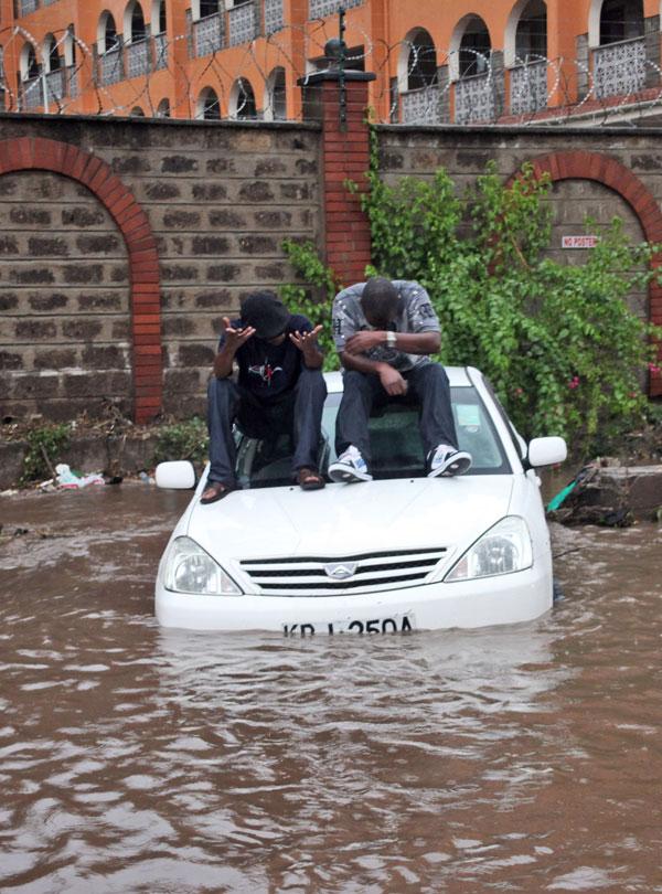 9. Два кенийца сидят на крыше своего автомобиля после сильного ливня в Найроби. (AP Photo/Sayyid Azim)