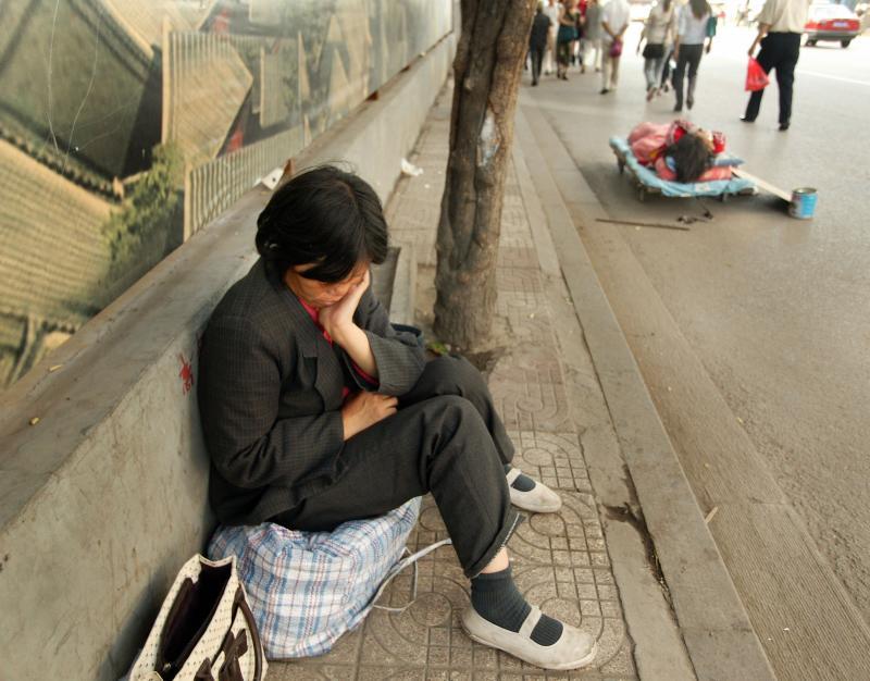 9) Уставшая и обезумевшая от горя мать сидит рядом со своей дочерью, лежащей на улице на самодельной кровати с написанной от руки табличкой о помощи в центре Пекина 4 сентября 2006 года. Крупные города Китая заполнили бедные, безработные и угнетенные люди, пришедшие в города в надежде найти более благоприятные условия для жизни, чем были в их бедных деревнях, особенно после того, как система социального обеспечения коммунистов исчезла. (UPI Photo/Stephen Shaver)