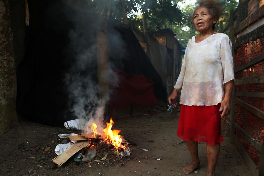 10. Женщина жжет мусор в бедном районе трущоб 2 декабря 2009 года в Рио-де-Жанейро. (Photo by Spencer Platt/Getty Images)