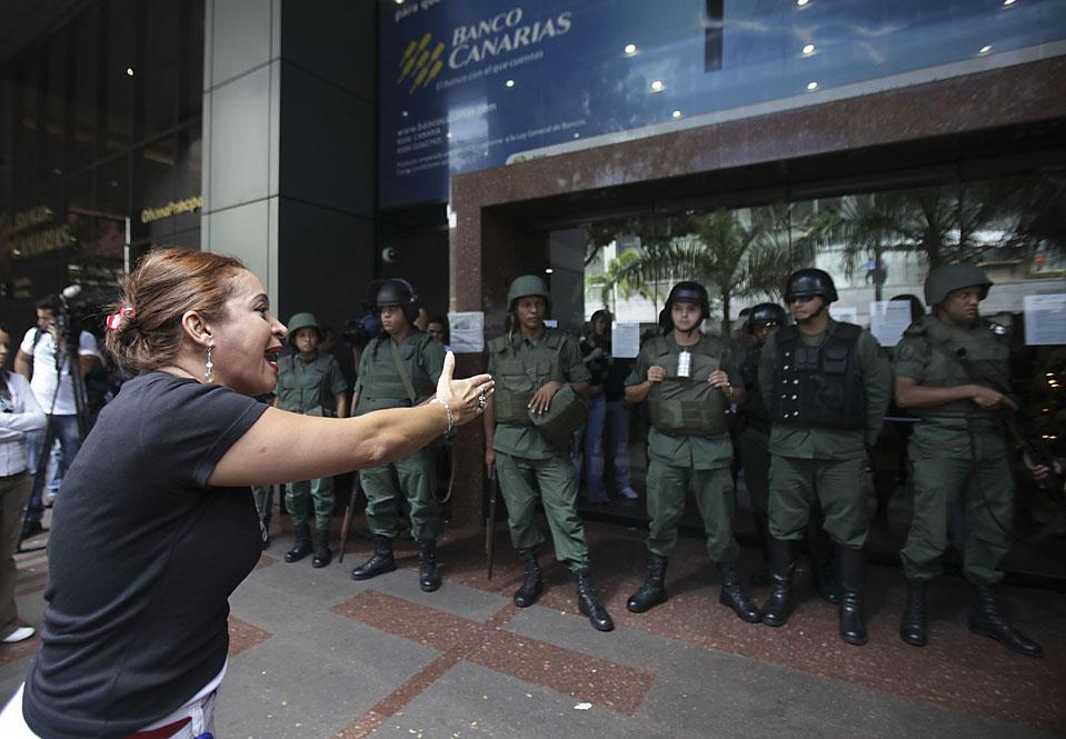 11) Сотрудница банка «Canarias» требует получения выходного пособия в Каракасе, Венесуэла. Правительство страны закрыло четыре небольших банка, объясняя свои действия многочисленными нарушениями. (Ариана Кубильос/Associated Press)