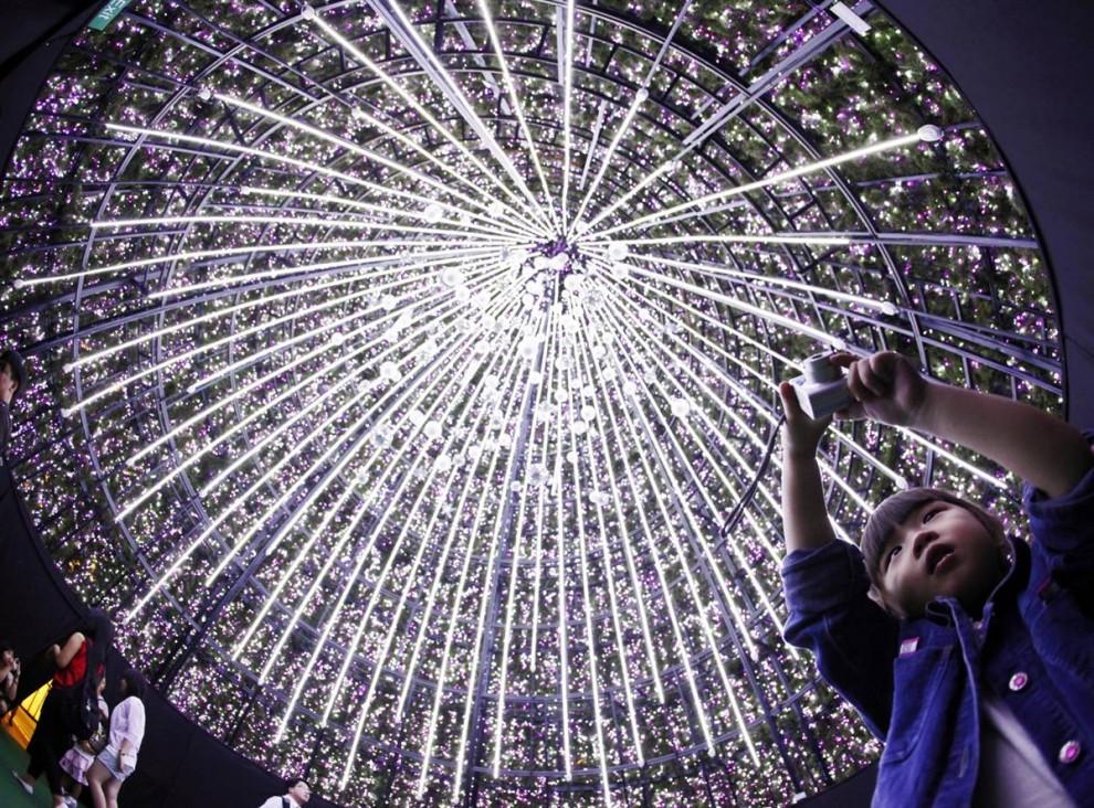 10. Дети фотографируют интерьер 6-этажной рождественской елки у торгового центра в Сингапуре 26 ноября. (How Hwee Young / EPA)