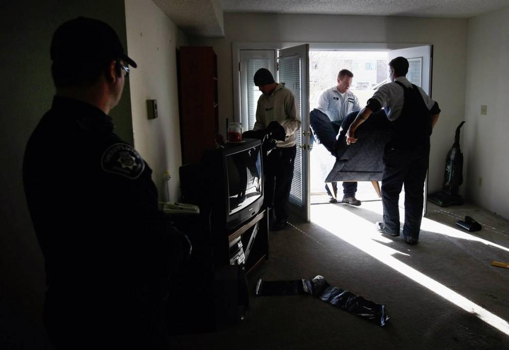 10) Заместитель шерифа наблюдает за тем, как команда по выселению выносит мебель из квартиры Лессера. (John Moore/Getty Images)