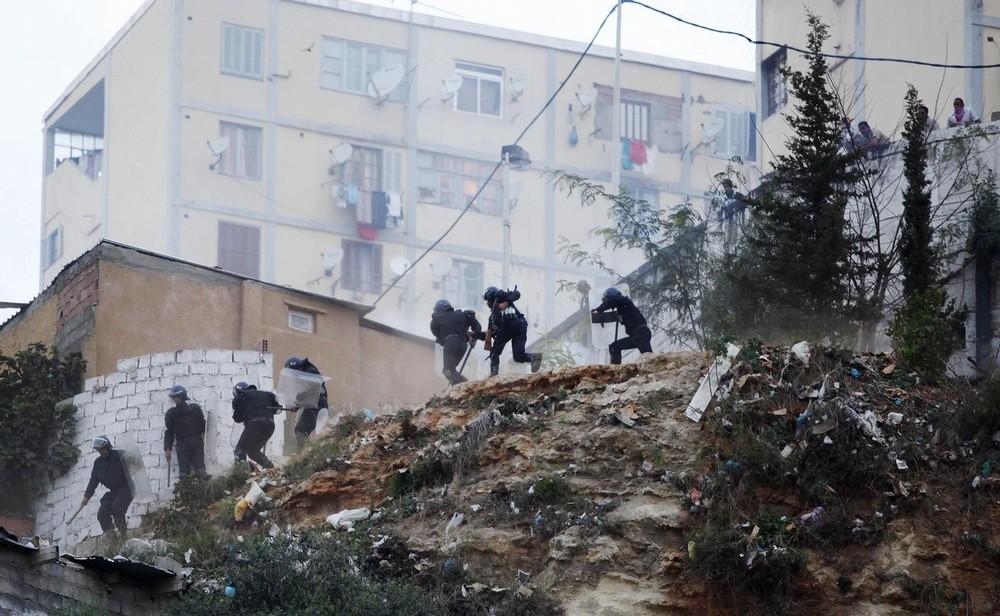 10. Алжирские полицейские бегут в укрытие во время столкновения с демонстрантами в округе Диар Эчамс в Алжире 20 октября 2009. Демонстранты бросали камни и бутылки с зажигательной смесью в полицию в столице Алжира на второй день протестов по поводу жилищных условий. (REUTERS/Louafi Larbi)