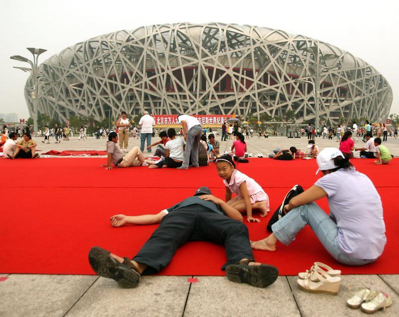 10) Китайцы отдыхают на огромном красном ковре перед Национальным стадионов Китая, который они ласково называют «Птичье гнездо» в парке Олимпик Грин в Пекине, 7 августа 2009 года. (UPI/Stephen Shaver)