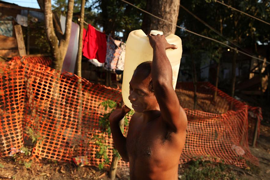11. Мужчина несет воду в дом, в котором нет водопровода, в бедном районе фавел «города Бога» 2 декабря 2009 года в Рио-де-Жанейро. (Photo by Spencer Platt/Getty Images)