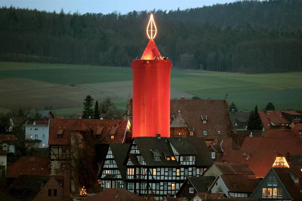 11. Шпиль украшен красной тканью, чтобы быть похожим на самую большую свечу в мире на Рождественском рынке в Шлице, Германия. Свеча сделана из каменной башни в 36 метров высотой и покрыта более 1000 кв.метров ткани. Около 140 лампочек освещают свечу на вершине в форме пламени. (Fredrik Von Erichsen / EPA)