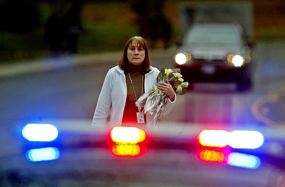 1) Cотрудница муниципалитета принесла цветы к штаб-квартире полиции в Лейквуде, штат Вашингтон, после того как в воскресенье в кофейне боевиком были убиты четыре сотрудника полиции. В Сиэтле в понедельник команда SWAT взяла штурмом один из домов, где, как полагали, находился подозреваемый. Но попытка не удалась, и стрелок все еще  остается на свободе. (Dean J. Koepfler/The News Tribune via Associated Press)