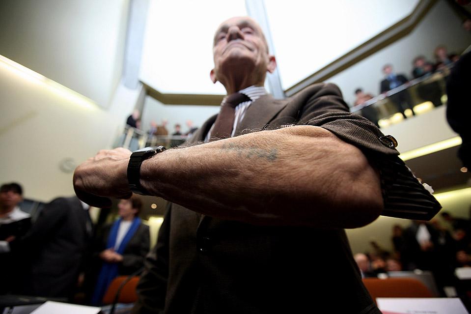4) Роберт Коэн показывает татуировку, которую ему сделали в концлагере  Аушвиц-Биркенау. Снимок сделан в зале суда в Мюнхене во время судебного разбирательства над Джоном Демьянюком, которого обвиняют в убийстве 27900 евреев. Демьянюк был депортирован из США в мае. Ему грозит до 15 лет тюремного заключения. (Miguel Villagran/Getty Images)