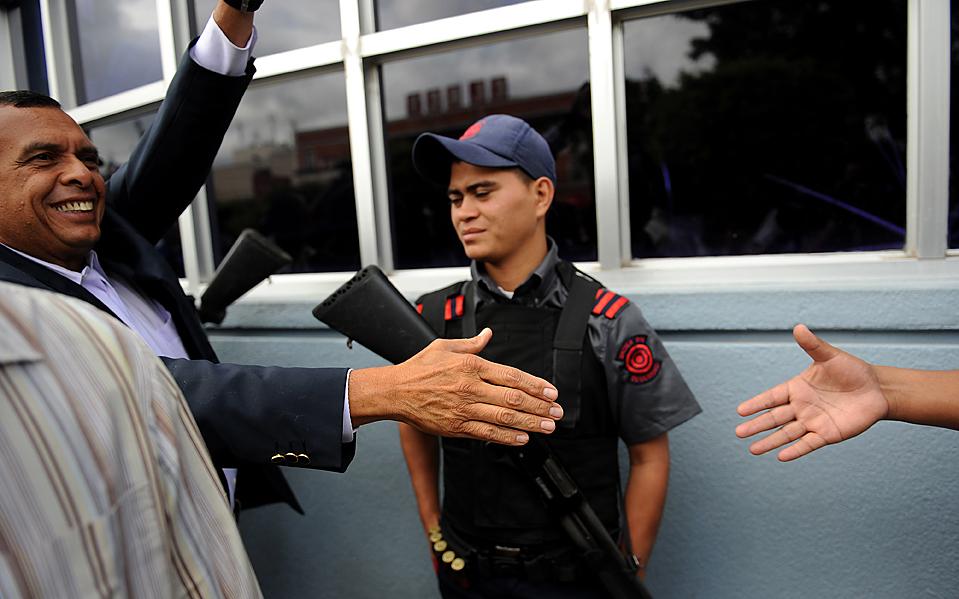 5) Новоизбранный президент Гондураса Порфирио Лобо, слева, пожимает руку своему стороннику в Тегусигальпе. Некоторые считают, что выборы дают шанс вывести страну из тупиковой ситуации, в которой она оказалась после свержения бывшего президента Мануэля Селаий летом. (Yuri Cortez/Agence France-Presse/Getty Images)