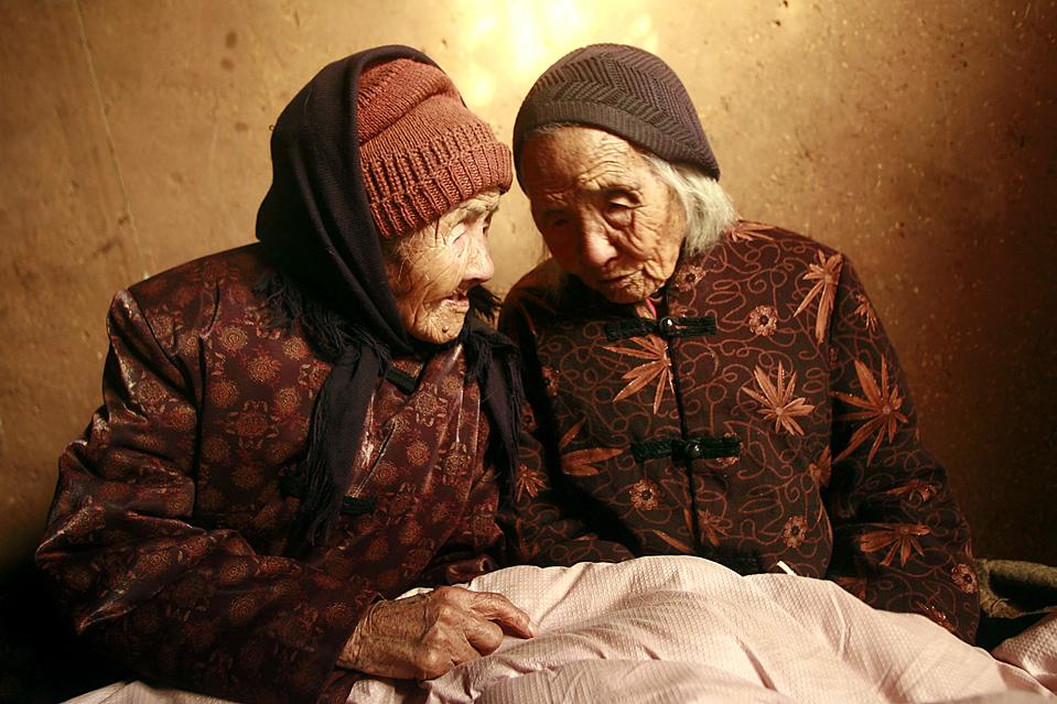 13) Близнецы Цао Сяоцяо, слева, и Цао Дацяо у себя дома в Вэйфан, в китайской провинции Шаньдун. Им 104 года, и согласно Книге рекордов Гиннеса, они являются самыми старыми ныне живущими близнецами. (Agence France-Presse/Getty Images)