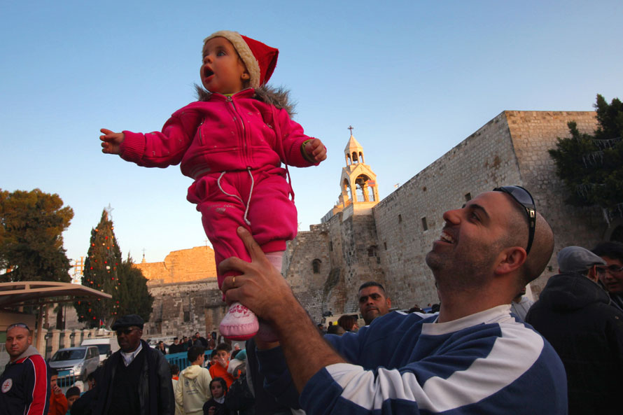 11. Палестинский христианин держит свою маленькую дочь над толпой, чтобы та увидела рождественское шоу на площади Мангер у Грота Рождества Христова в Вифлееме. (Photo by David Silverman/Getty Images)