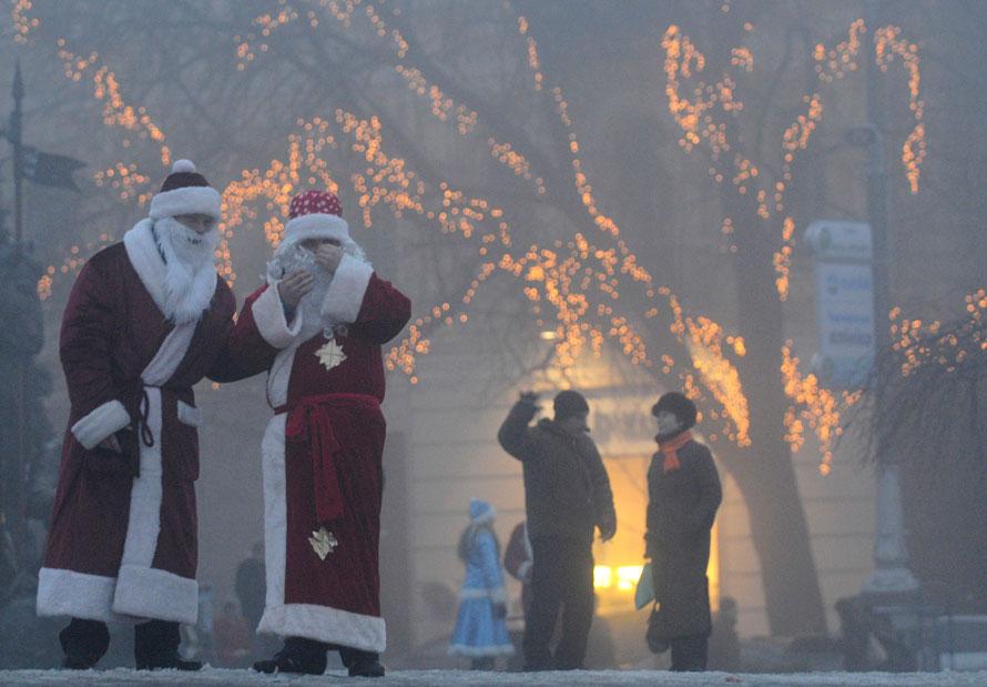 11. Два человека в костюмах Деда Мороза разговаривают на улице в Киеве. (AP Photo/Sergei Chuzavkov)