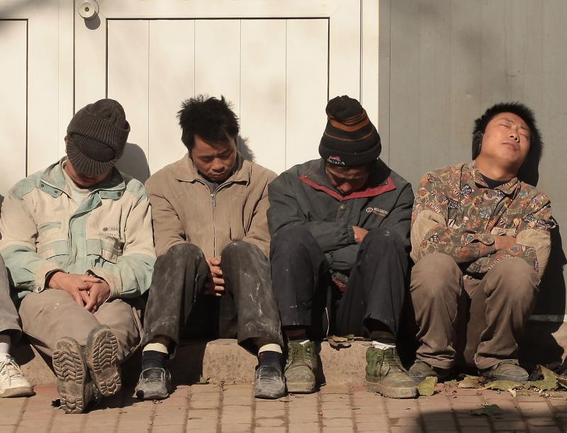 11) Китайские рабочие-мигранты греются на солнце во время обеденного перерыва в прохладный день в Пекине 21 ноября 2009 года. В то время как китайская экономика в целом процветает, миграционная рабочая сила серьезно пострадала в отсутствии надежды на облегчение условий труда. (UPI/Stephen Shaver)