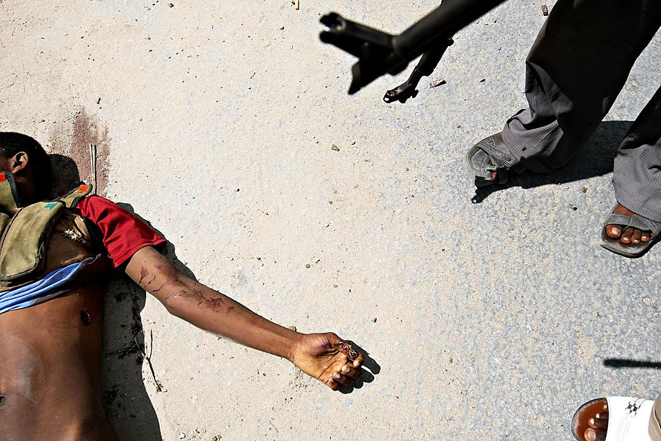 3) Солдат правительственной армии стоит рядом с телом исламского боевика в столице Сомали Могадишо. Боевики атаковали позиции правительственных войск рано утром во вторник. (Mohamed Dahir/Agence France-Presse/Getty Images)
