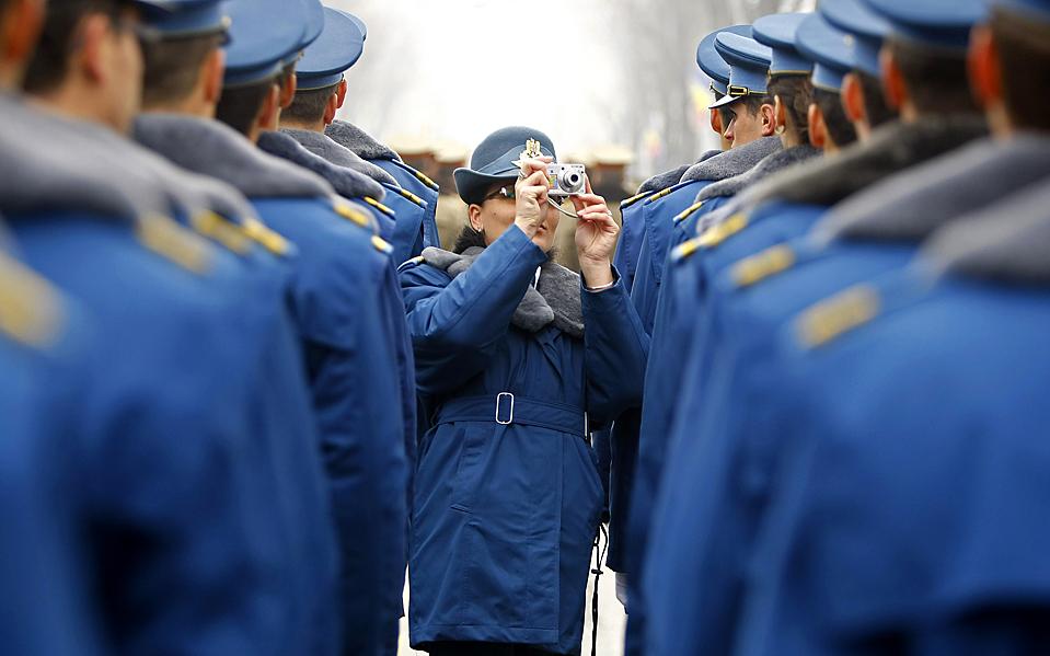 9) Солдат фотографирует своих сослуживцев перед военным парадом в Румынии по случаю Национального праздника в Бухаресте. (Bogdan Cristel/Reuters)