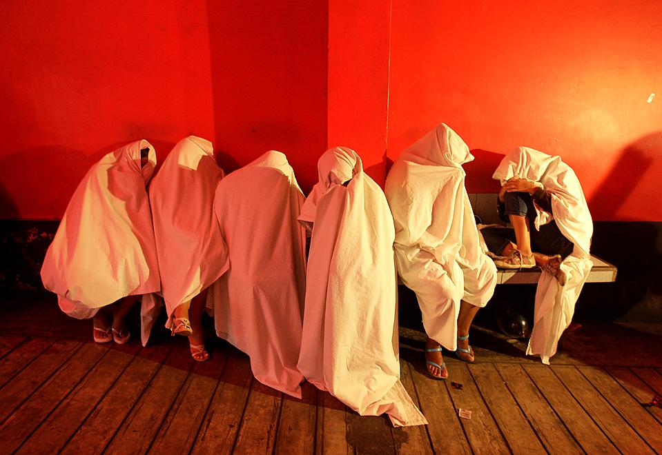 10) Проститутки закрываются от объектива, перед прохождением тестирования на ВИЧ в публичном доме в Кальяо, Перу. Во вторник во всем мире отметили  Всемирный день борьбы со СПИДом. (Martin Mejia/Associated Press)