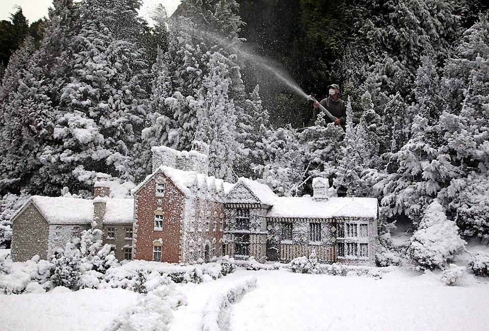 11) Стив Хэнлон распыляется искусственный снег над моделью деревни Баббакомбе в Торки, Великобритания. Это место является туристической достопримечательностью. (Matt Cardy/Getty Images)
