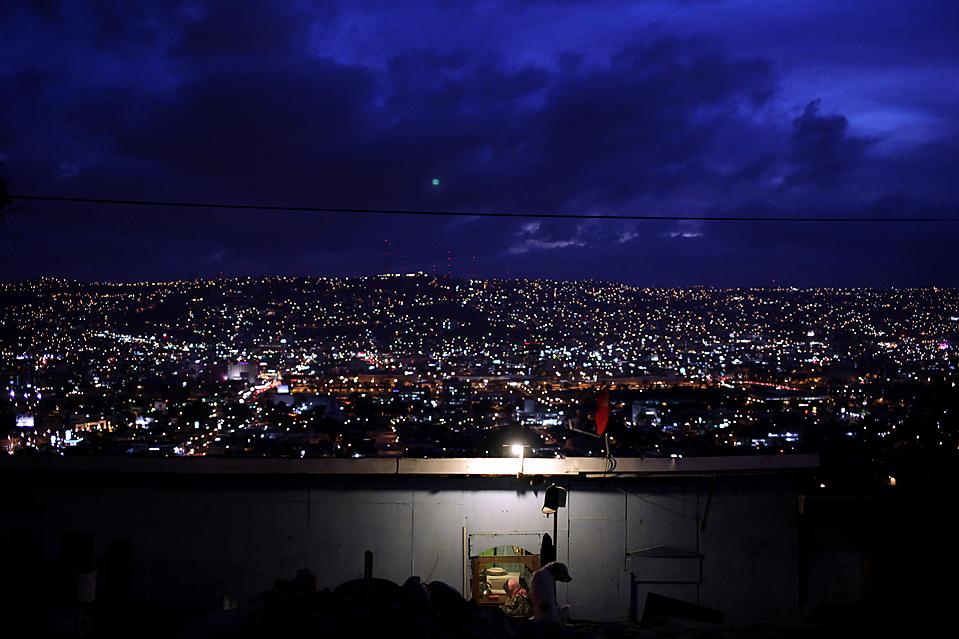 6) Женщина сидит у себя дома в районе Ла-Либертад в пограничном городе Тихуана, Мексика. (Guillermo Arias/Associated Press)