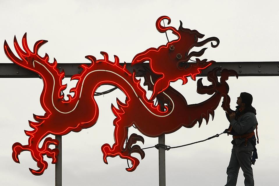 11) Работник проверяет подключение на логотипе, изображающем Красного дракона, который расположен на китайском рынке вблизи Бухареста. Сотни мелких магазинов на этом рынке будут закрыто, чтобы освободить место для строительства. (Bogdan Cristel/Reuters)