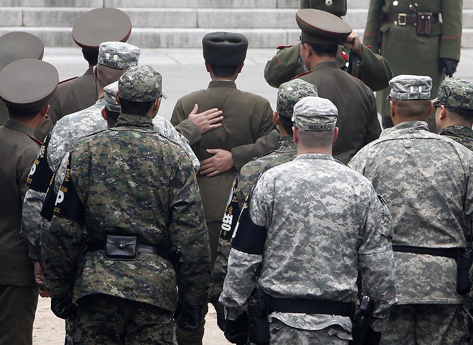 16) Северокорейские солдаты помогают своему товарищу в пограничной деревне Пханмунджом. Сержант армии, в центре снимка, был репатриирован по его просьбе после того, как южнокорейцы спасли его, дрейфующего на маленькой лодке вблизи южнокорейского острова Yeonpyeong 29 ноября. (Jo Yong-Hak/Reuters)