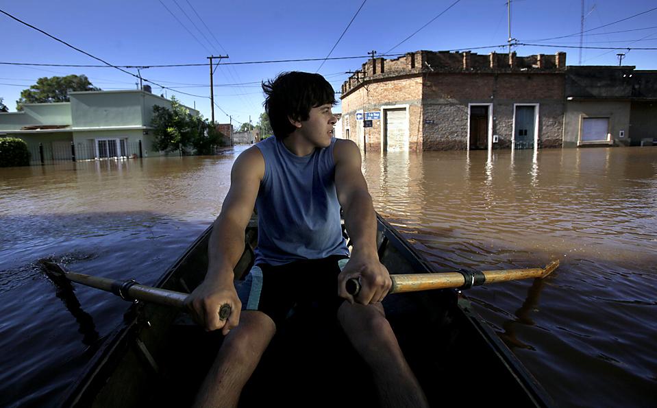 3) Человек плывет через затопленную улицу в Конкордия, Аргентина. Проливные дожди вызвали половодье на реке Уругвай, в результате чего местные жители вынуждены были эвакуироваться. (Наташа Писаренко/Associated Press)
