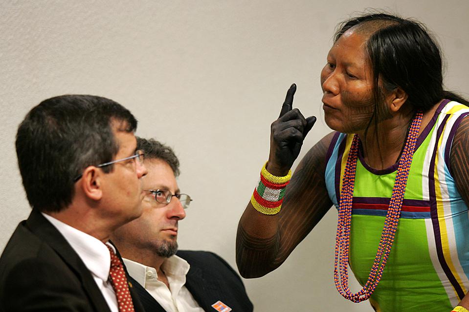 5) Туйра Кайапо, вождь племени Кайапо, разговаривает с Алойзью Гуапиндайя, слева, директором Бразильского Национального фонда индейцев в ходе публичных слушаний в городе Бразилиа. Коренные жители выступили против решения правительства о строительстве  гидроэлектростанции Бело Монте. (Eraldo Peres/Associated Press)