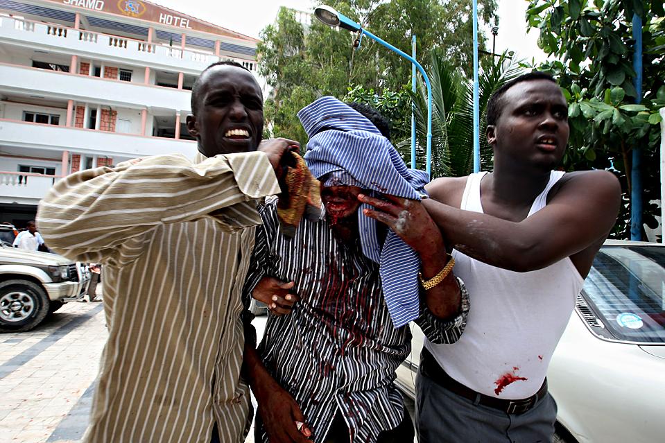 9) Оказание помощи раненому, который пострадал в результате атаки смертника, одетого как женщина, взорвавшего себя во время церемонии по случаю окончания университета в Могадишо. В результате нападения были убиты более 19 человек, включая трех членов кабинета министров, врачей и студентов-медиков. (Mohamed Dahir/Agence France-Presse/Getty Images)