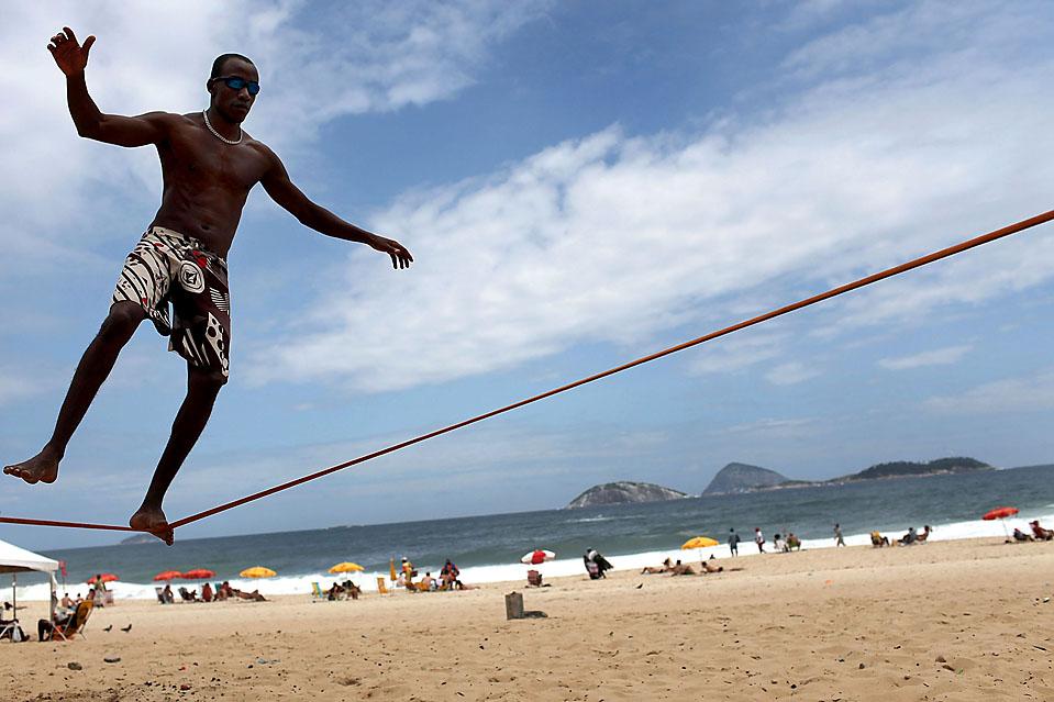 16. Джедсон Гил упражняется в «канатоходстве», которое сравнивают с серфингом в небе. Снимок сделан на пляже в Рио-де-Жанейро. (Spencer Platt/Getty Images)