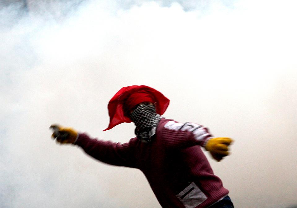 12. Курдский демонстрант бросает камень в отряд турецкой штурмовой полиции во время демонстраций в Диярбакыре, Турция. Курдский народ протестовал против политики турецкого правительства в отношении курдов.