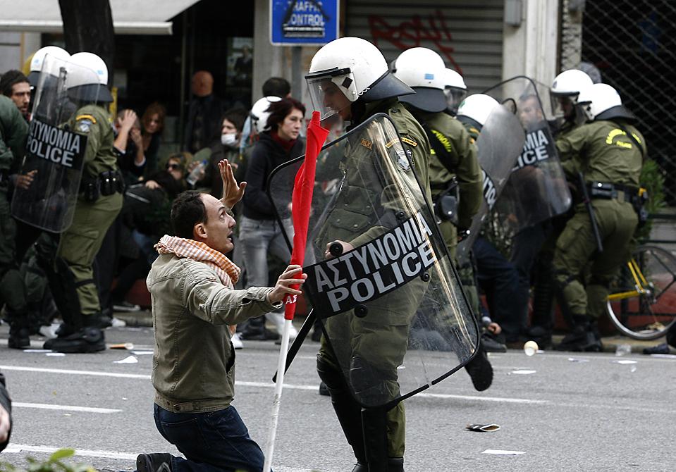 13. Демонстрант стоит на коленях перед полицейским в Афинах. Демонстранты бросали камни и коктейли Молотова в полицию во время беспорядков в память о годовщине смерти 15-летнего подростка Александроса Григоропулоса, которого полицейский застрелил год назад. (Kostas Tsironis/Associated Press)