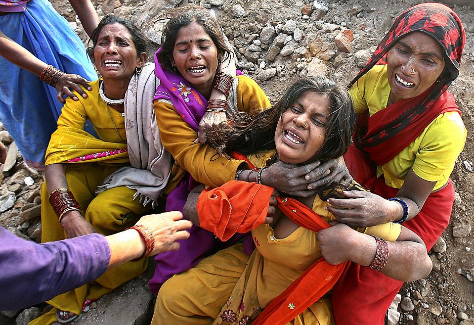 15. Родственники жертв несчастного случая на стройке в индийском городе Чандигарх. По меньшей мере, шестеро рабочих погибло после того, как перевернулся грузовик, груженный глиной. (Ajay Verma/Reuters)