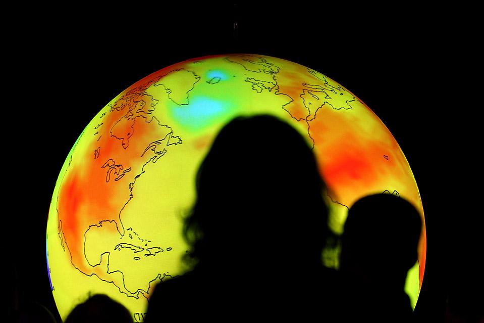2) Люди наблюдают за анимационной проекцией, которая демонстрирует влияние изменения климата. Снимок сделан во время конференции ООН по изменению климата в Копенгагене во вторник. В понедельник прошло открытие конференции, в которой приняли участие представители из 192 стран. (Miguel Villagran/Getty Images)