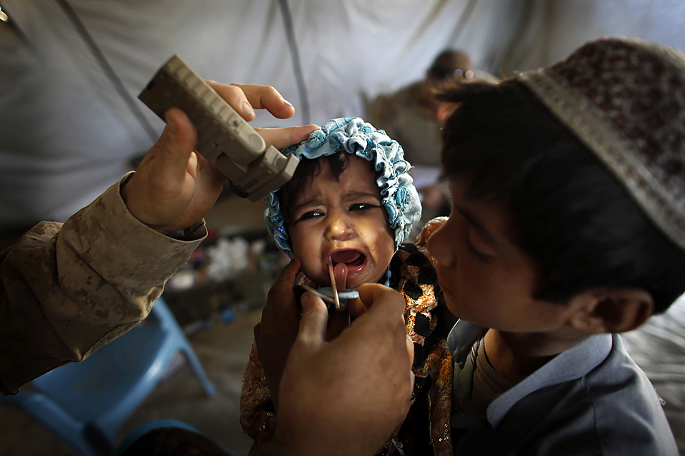 4) Представитель медицинского персонала ВМС США дает маленькой девочке лекарства в бесплатной клинике в афганском городе Хан Нешин. Клиника предоставляет лекарства и медицинскую помощь местному населению. (Kevin Frayer/Associated Press)