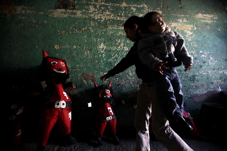 """14) Женщина устанавливает чучела дьявола, которые должны быть сожжены во время ежегодной церемонии """"Сожжения дьявола"""", на заводе города Гватемала. В этом году правительство страны попросило участников многовекового христианского праздника не зажигать традиционных больших костров, чтобы избежать выбросов углекислого газа. (Daniel LeClair/Reuters)"""