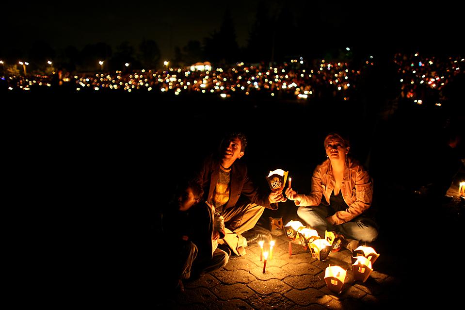 15) Люди держат свечи во время празднования Дня свечи, который по традиции открывает рождественский сезон в Боготе, Колумбия. (William Fernando Martinez/Associated Press)