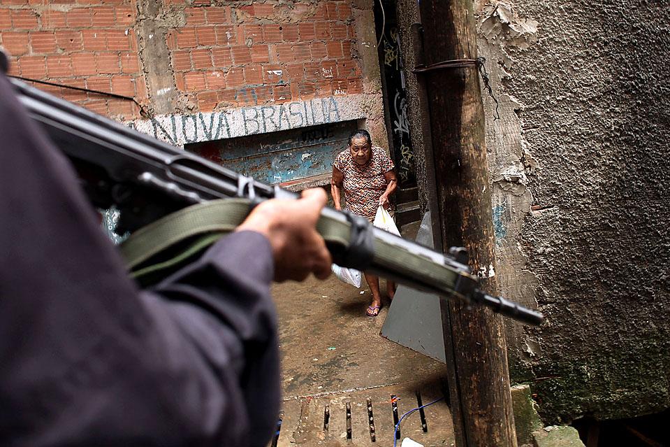 """5) Старушка идет во время спецоперации в трущобах """"Копакабана"""" в Рио-де-Жанейро, которые члены специального полицейского батальона провели в поисках оружия и наркотиков. По данным Бразильского института географии и статистики, в среднем в период между 1998 и 2008 годов погибали каждый день68 молодых бразильцев. Эта цифра включает убийства, случаи бандитизма и дорожно-транспортные происшествия. (Spencer Platt/Getty Images)"""