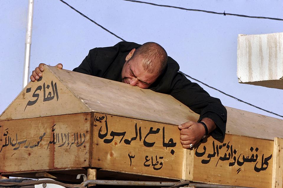 7) 37-летний Маджид Хасан плачет над гробом своей жены во время похорон в святом шиитском городе Эн-Наджаф в Ираке. Она была одной из 127 убитых в нескольких взрывах, которые прогремели в Багдаде во вторник. (Alaa al-Marjani/Associated Press)