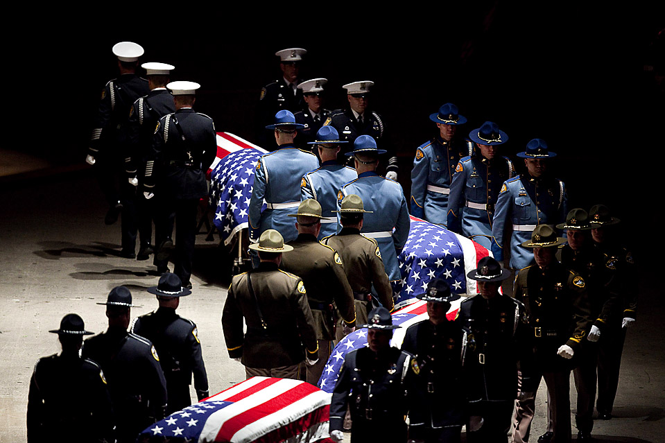 8) Сотрудники полиции окружили гробы укрытые флагами во время похорон сержанта  Марка Реннингера и офицеров Рональда Оуэнса, Тины Крисволд и Грега Ричардса из Лейквуда, штат Вашингтон. Во время похорон, которые прошли в Такоме во вторник, присутствовали 20 тысяч человек. Власти сообщают, что убийца, застреливший сотрудников полиции в кафе 29 ноября, Морис Клеммонс, позднее был смертельно ранен. (Stephen Brashear/Getty Images)