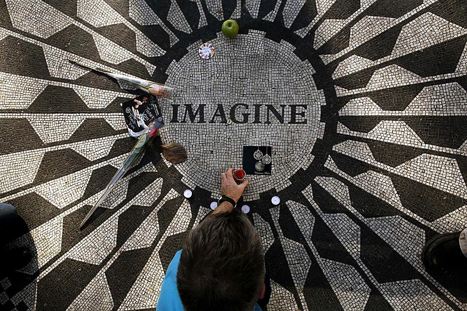"""13) Турист ставит свечу на мозаику """"Imagine"""" на Мемориале Strawberry Fields в Центральном парке Нью-Йорка к 29-летию со дня смерти бывшего битла Джона Леннона. (Брендан McDermid/Reuters)"""