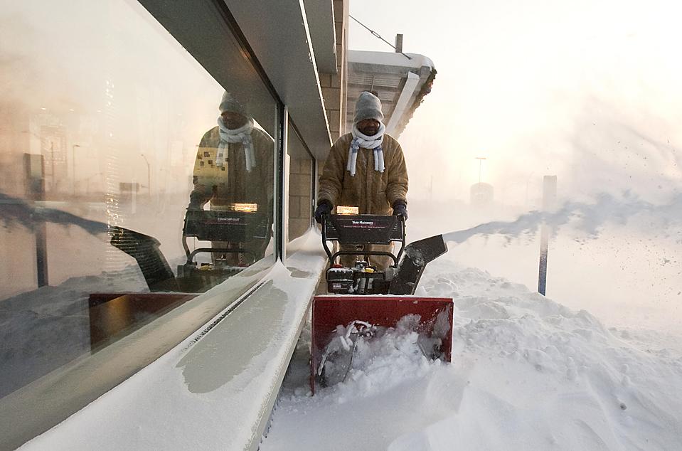 16) Рабочий чистит тротуар от снега в городе Омаха, штат Небраска. В восточной части штата в результате сильного ветра и ночного снегопада, уровень снега составил более 30 см. (Nati Harnik/Associated Press)