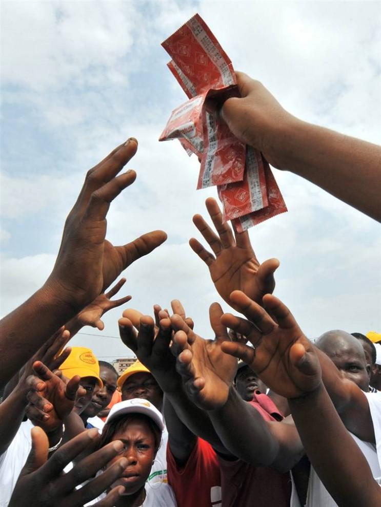 12. Девушка раздает презервативы в Йопугоне – рабочем районе столицы Абиджан – во время акции против СПИДа для пяти миллионов людей в пяти западноафриканских странах: Кот-д'Ивуар, Гана, Того, Бенин и Нигерия. (Sia Kambou / AFP - Getty Images)
