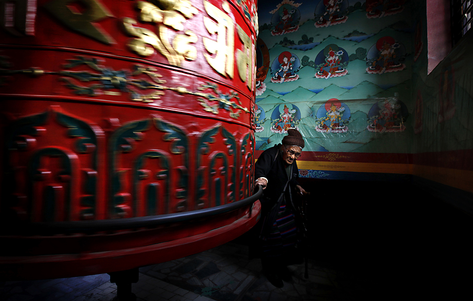 4) Старушка вращает гигантское колесо в ступе Буддханат, в Непале. (Gemunu Amarasinghe/Associated Press)