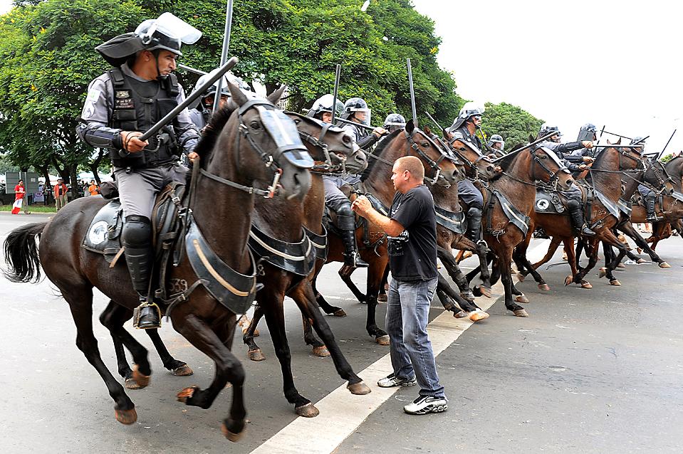 7) Студент стоит напротив полицейских лошадей во время демонстрации протеста против губернатора округа Жозе Роберто Арруда в городе Бразилиа, Бразилия. Существует видео, на котором видно как Арруда берет взятку во время кампании 2006 года. (Evaristo Sa/Agence France-Presse/Getty Images)