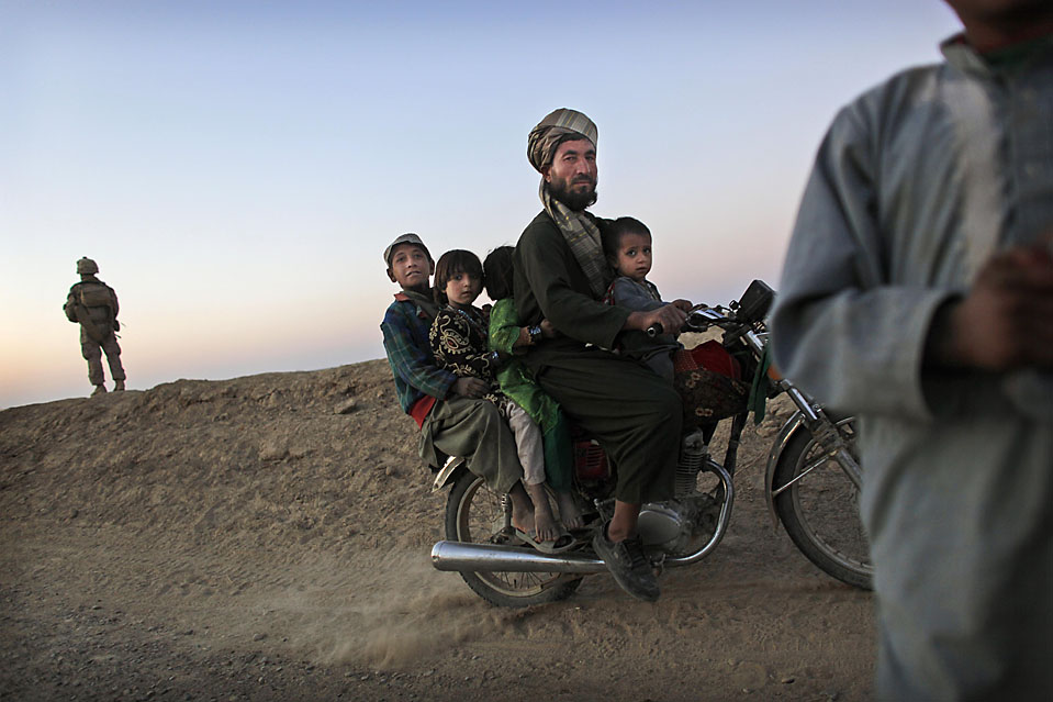 13) Афганская семья проезжает мимо патруля американских морских пехотинцев. Снимок сделан в неспокойной афганской провинции Гильменд. (Кевин Frayer/Associated Press)