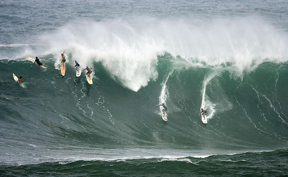 15) Пять серфингистов опускаются по гребню волны в заливе Ваймеа, расположенном на северном берегу острова Оаху, Гавайи. (Eugene Tanner/Associated Press)