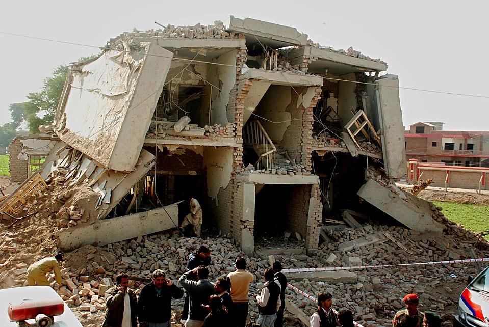 12) Пакистанские военные осматривают здание, разрушенное взрывом заминированного грузовика во вторник. В результате данного теракта по меньшей мере 12 человек, включая четырех солдат, были убиты и более 30 человек ранены. (M.K. Chaudhry/EPA)