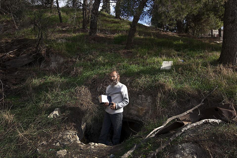 11) Владимир Карпин, христианский паломник из России, держит в руках Новый Завет, стоя у входа в пещеру в Елеонской горе, которая является его временным домом, Иерусалим, Израиль. Карпин заявил, что он решил жить в пещере до второго пришествия Мессии. (Menahem Kahana/AFP/Getty Images)