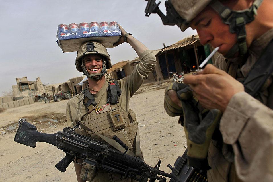 9) Американские морские пехотинцы Ланс Грэйсон Барнетт из Мэриленда (слева) и Ланс Майкл Домбровски (справа) обсуждают как они делали покупки на рынке после патрулирования в Хан Нешине, Афганистан. (Kevin Frayer/Associated Press)